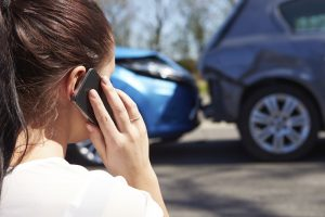 A woman calls her insurance company after an auto collision