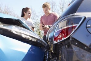 Two drivers exchange auto insurance information after a collision