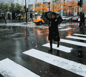 A pedestrian walks through a crosswalk